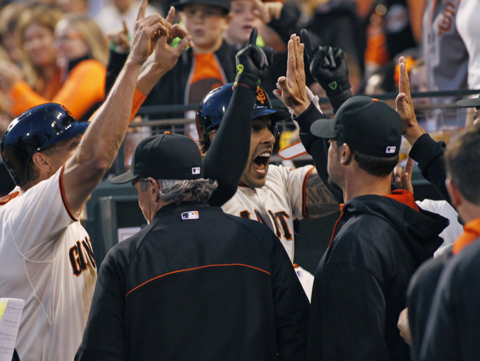 Photo - San Francisco Giants' Michael Morse celebrates in the dugout after hitting a two-run home run against the Miami Marlins during the third inning of a baseball game, Thursday, May 15, 2014, in San Francisco. (AP Photo/George Nikitin)