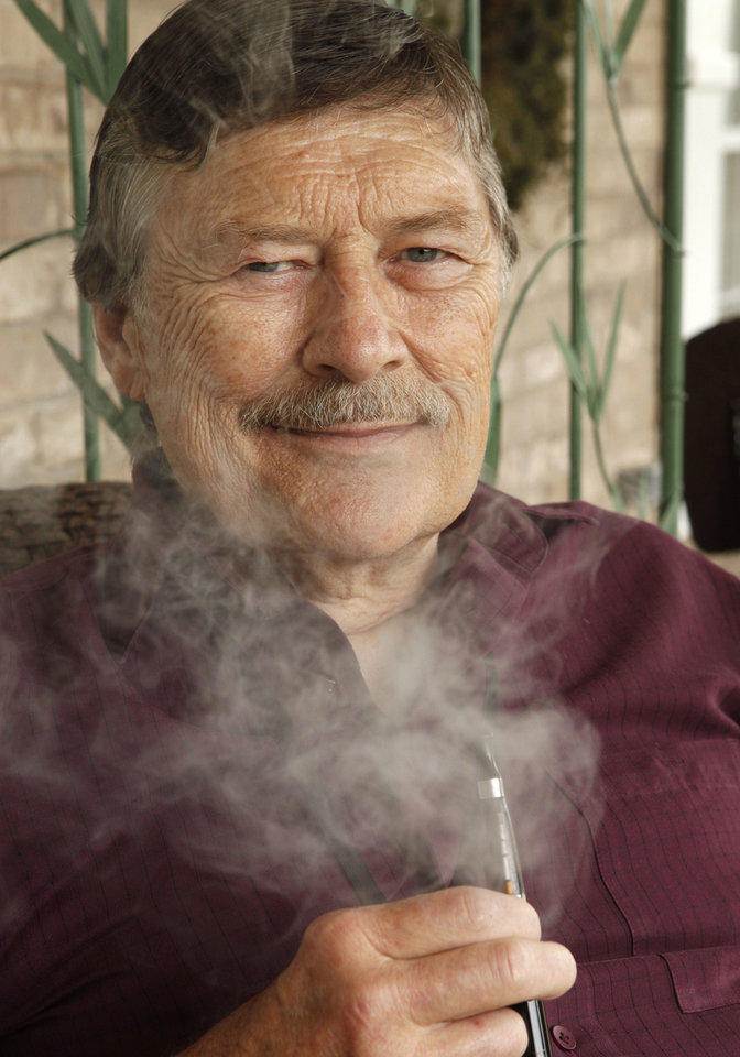 Bob Clark demonstrates his e-cigarette that he is using to quit smoking at his home in Edmond. Clark has smoked for the past 50 years but hopes to quit this month. <strong>PAUL HELLSTERN - Oklahoman</strong>