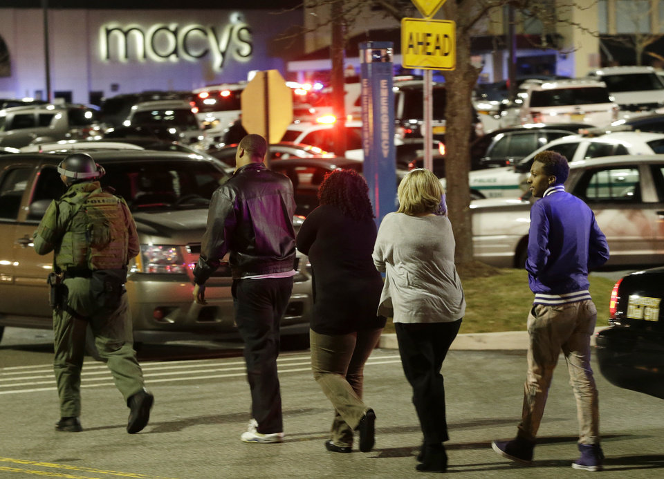 Photo - An official, left, wearing tactical gear leads a group of people out of the Garden State Plaza Mall during a lockdown following reports of a shooter, Tuesday, Nov. 5, 2013, in Paramus, N.J. (AP Photo/Julio Cortez)