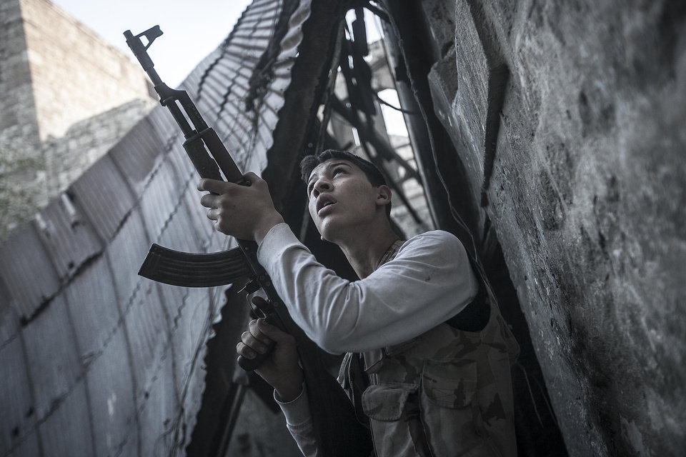 Photo -   In this Saturday, Nov. 03, 2012 photo, a rebel fighter watches windows in an overlooking building as he awaits for loyalists to President Bashar Assad to appear during heavy fighting in the Jedida district of Aleppo, Syria.(AP Photo/Narciso Contreras)