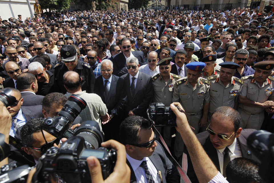 Photo - Egyptian Interior Minister Mohammed Ibrahim, center, and top officers of the army and police, march during a military funeral of policemen killed during Wednesday's clashes in Cairo, Egypt, Thursday, Aug. 15, 2013. Egyptian authorities on Thursday significantly raised the death toll from clashes the previous day between police and supporters of the ousted Islamist president, saying hundreds of people died and laying bare the extent of the violence that swept much of the country and prompted the government to declare a nationwide state of emergency and a nighttime curfew. (AP Photo/Amr Nabil)