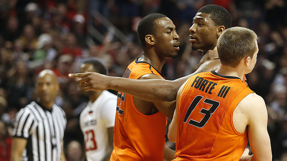 Oklahoma State's Markel Brown(22) and Phil Forte(13) hold Marcus Smart(33) after Smart shoved a fan during their NCAA college basketball game in Lubbock, Texas, Saturday, Feb, 8, 2014. (AP Photo/Lubbock Avalanche-Journal, Tori Eichberger) ALL LOCAL TV OUT