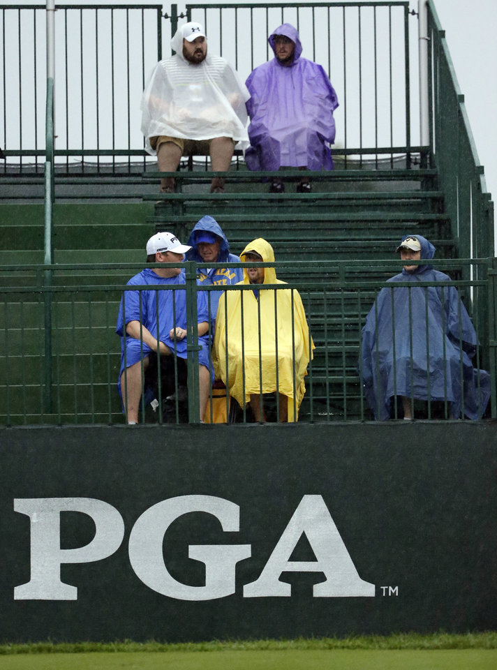 Photo - Golf fans sit in the rain on range before the second round of the PGA Championship golf tournament at Valhalla Golf Club on Friday, Aug. 8, 2014, in Louisville, Ky. (AP Photo/David J. Phillip)