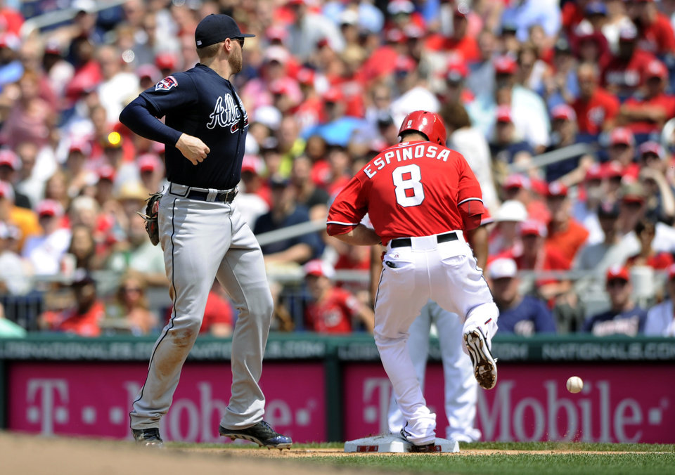 Photo - Washington Nationals' Danny Espinosa (8) is safe at first against Atlanta Braves first baseman Freddie Freeman, left, during the fourth inning of a baseball game, Sunday, June 22, 2014, in Washington. (AP Photo/Nick Wass)