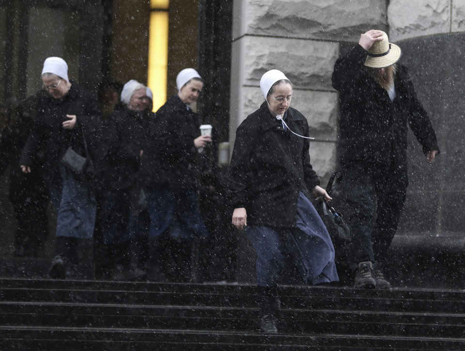 Photo - Amish men and women leave the U.S. Federal courthouse Friday, Feb. 8, 2013, in Cleveland. Sam Mullet Sr., 67, the ringleader in a series of unusual hair- and beard-cutting attacks on fellow Amish religious followers in the U.S., was sentenced Friday to 15 years in prison, and 15 family members received sentences of one year to seven years. The defendants were charged with a hate crime because prosecutors believe religious differences brought about the attacks. (AP Photo/Tony Dejak)