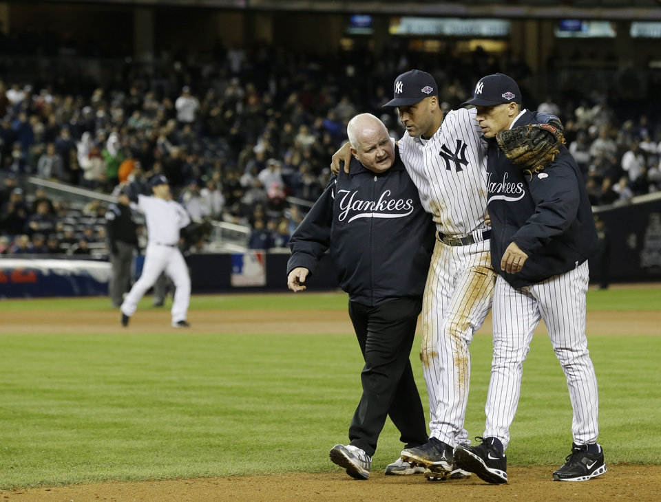Photo -   Trainer Steve Donohue, left, and New York Yankees manager Joe Girardi, right, help Derek Jeter off the field after he injured himself during Game 1 of the American League championship series against the Detroit Tigers Sunday, Oct. 14, 2012, in New York. (AP Photo/Paul Sancya )