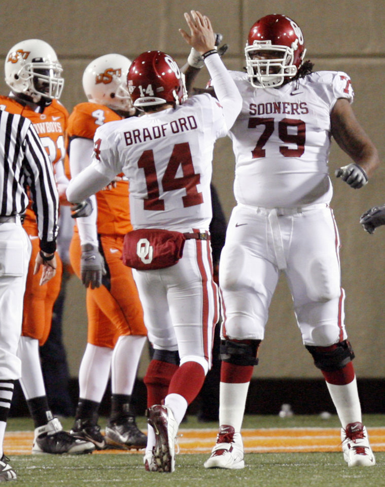 Photo - Oklahoma's Sam Bradford (14) and Phil Loadholt (79) give high fives after an OU touchdown during the second half of the college football game between the University of Oklahoma Sooners (OU) and Oklahoma State University Cowboys (OSU) at Boone Pickens Stadium on Saturday, Nov. 29, 2008, in Stillwater, Okla. STAFF PHOTO BY CHRIS LANDSBERGER