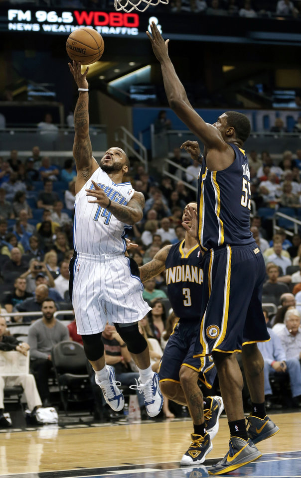 Orlando Magic's Jameer Nelson (14) gets around Indiana Pacers' George Hill (3) and Roy Hibbert, right, for a shot during the first half of an NBA basketball game, Wednesday, Jan. 16, 2013, in Orlando, Fla. (AP Photo/John Raoux)