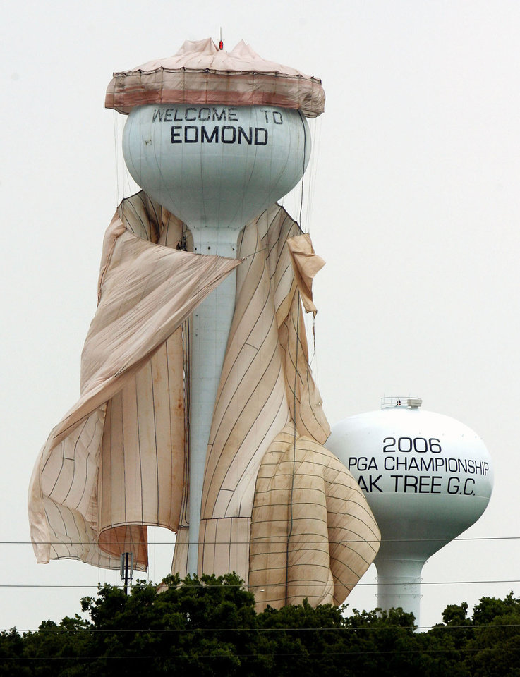 Photo - HONORABLE MENTION-FEATURE Workers try their best to get a containment shroud under control after high winds loosened the guy-lines around the water tower at I-35 and 2nd Street in Edmond, OK, Friday, May 8, 2009. Photo by Paul Hellstern, The Oklahoman