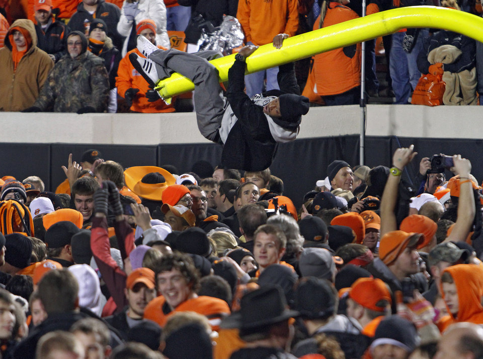 Photo - An Oklahoma State fan rides the goal post after the Cowboys' 44-10 win over Oklahoma during the Bedlam college football game between the Oklahoma State University Cowboys (OSU) and the University of Oklahoma Sooners (OU) at Boone Pickens Stadium in Stillwater, Okla., Saturday, Dec. 3, 2011. Photo by Chris Landsberger, The Oklahoman