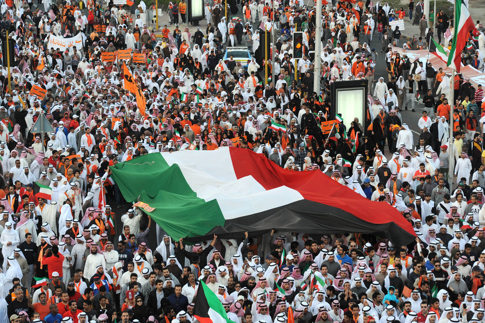 Islamist, nationalist and liberal opposition groups carry a large national flag as they gather to protest the Kuwait government's amendment of the electoral law and support a boycott on the country's election on Friday, Nov. 30, 2012 in Kuwait City. More than 15,000 protesters rallied in the first government-authorized demonstration in Kuwait since a ban on political gatherings earlier this month. The election to be held Saturday, Dec. 1 is the fifth since mid-2006, and the second this year.(AP Photo/Gustavo Ferrari)