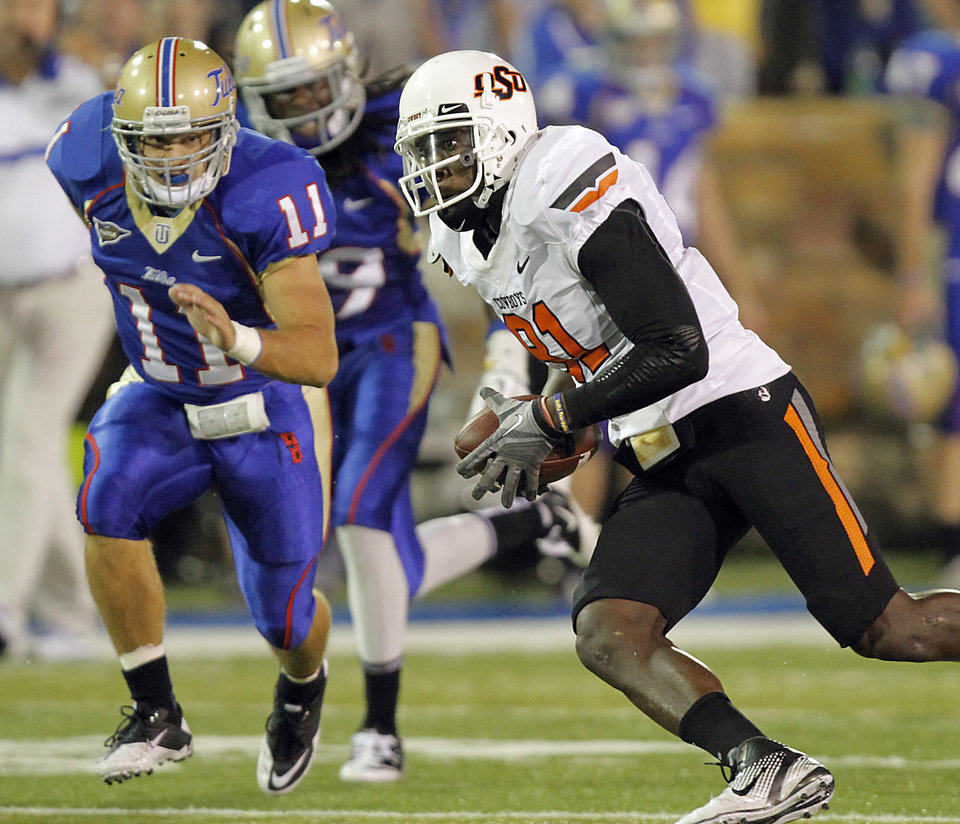 Photo - Oklahoma State's Justin Blackmon (81) runs past Tulsa's Alan Dock (11) during a college football game between the Oklahoma State University Cowboys and the University of Tulsa Golden Hurricane at H.A. Chapman Stadium in Tulsa, Okla., Sunday, Sept. 18, 2011. Photo by Chris Landsberger, The Oklahoman