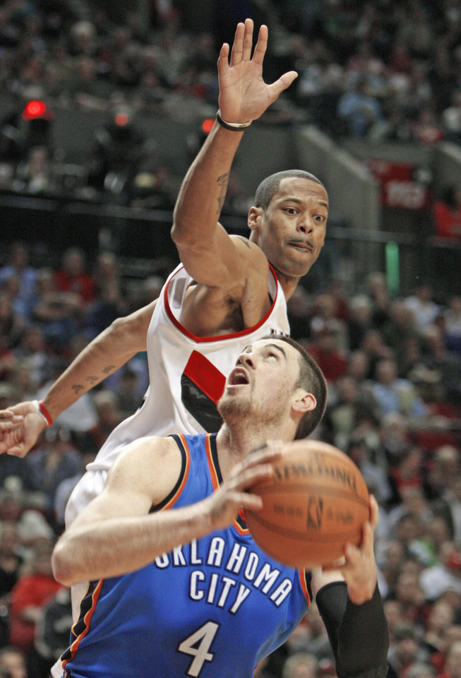 Photo - Oklahoma City's Nick Collison, front, looks at the basket as Portland's Marcus Camby defends during action on Monday in Portland, Ore. AP photo