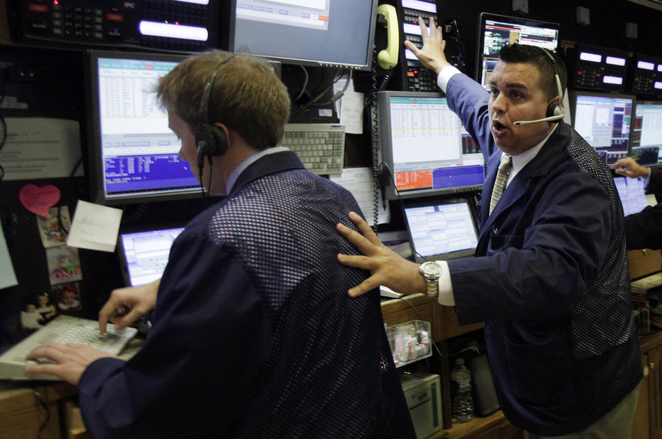 Photo -   A trader works in his booth on the floor of the New York Stock Exchange Thursday, July 26, 2012. U.S. stocks are soaring at the opening bell after the president of the European Central Bank vowed to do what it takes to preserve the continent's monetary union. (AP Photo/Richard Drew)