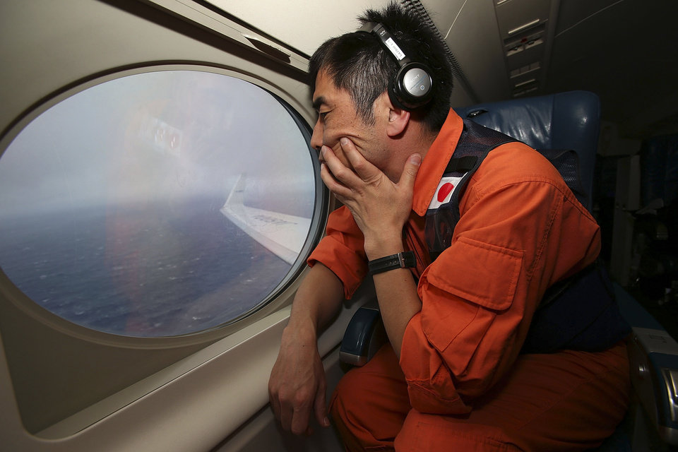Photo - Koji Kubota of the Japan Coast Guard keeps watch through a window of their Gulfstream V aircraft while flying in the search zone for debris from the missing Malaysia Airlines flight MH370 Tuesday, April 1, 2014 off Perth, Australia. Investigators are conducting a forensic examination of the final recorded conversation between ground control and the cockpit of the Malaysian plane before it went missing three weeks ago, the Malaysian government said Tuesday. Meanwhile Australia, which is coordinating the search for the Boeing 777, cautioned that it