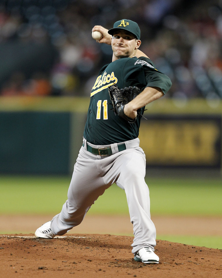 Photo - Oakland Athletics' Jarrod Parker throws in the first inning against the Houston Astros during a baseball game on Tuesday, July 23, 2013, in Houston. (AP Photo/Bob Levey)
