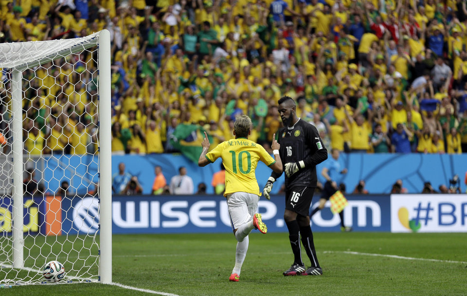 Photo - Brazil's Neymar runs past Cameroon's goalkeeper Charles Itandje after scoring his side's first goal during the group A World Cup soccer match between Cameroon and Brazil at the Estadio Nacional in Brasilia, Brazil, Monday, June 23, 2014. (AP Photo/Natacha Pisarenko)