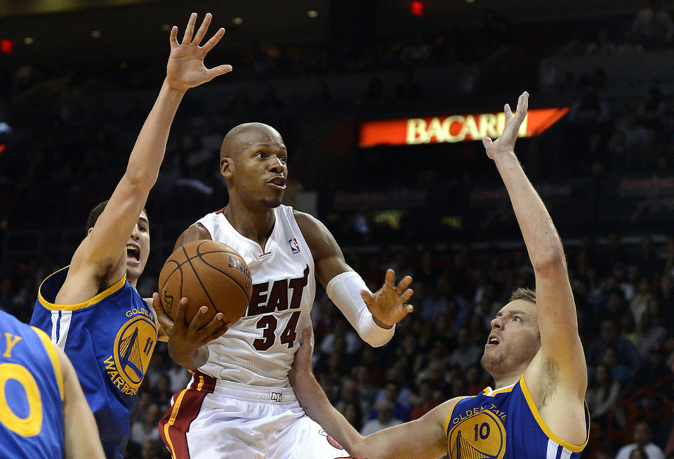 Miami Heat's Ray Allen (34) is defended by Golden State Warriors' Klay Thompson (11) and David Lee (10) during an NBA basketball game on Wednesday, Dec. 12, 2012, in Miami. (AP Photo/Rhona Wise)