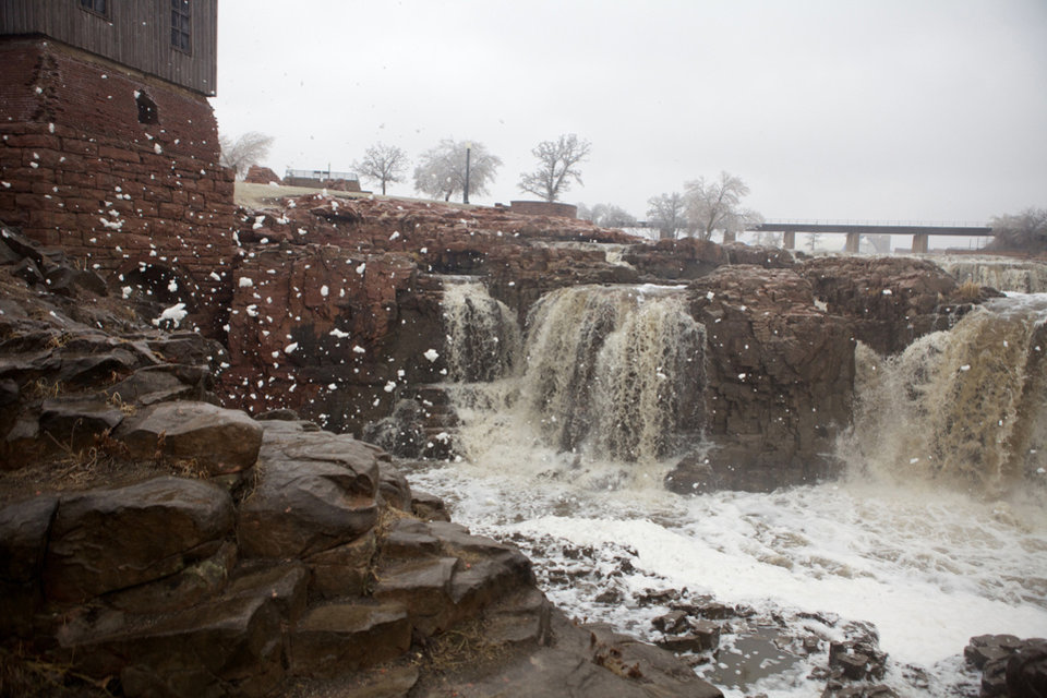 Foam is kicked up by strong wind gusts at The Falls Park in Sioux Falls, S.D., where a spring storm drove away visitors from the usually popular tourist attraction on Tuesday, April 9, 2013. The ice storm wreaked havoc on roads, downed branches and knocked out power for thousands of residents. The National Weather Service predicted that a half-inch of ice would accumulate by day\'s end. Other parts of the state were grappling with large amounts of snow. (AP Photo/Amber Hunt)