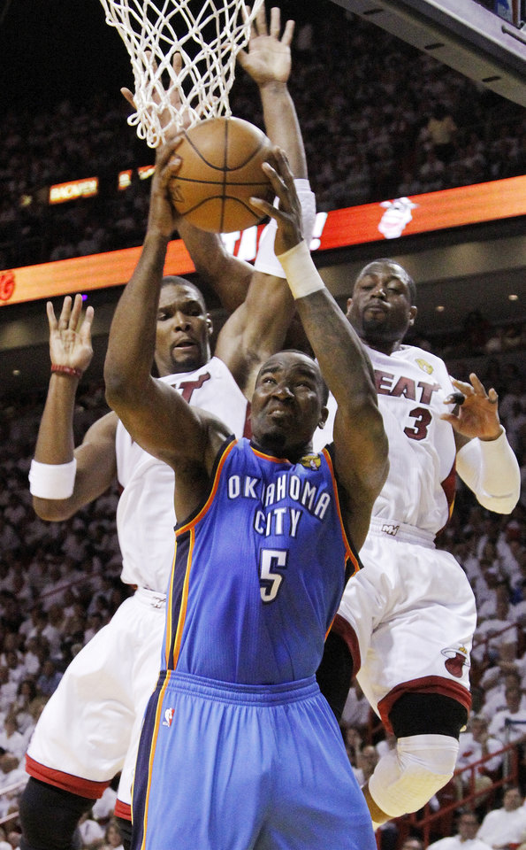 Oklahoma City\'s Kendrick Perkins (5) works underneath the basket as Miami\'s Chris Bosh (1) and Miami\'s Dwyane Wade (3) defend during Game 3 of the NBA Finals between the Oklahoma City Thunder and the Miami Heat at American Airlines Arena, Sunday, June 17, 2012. Photo by Bryan Terry, The Oklahoman