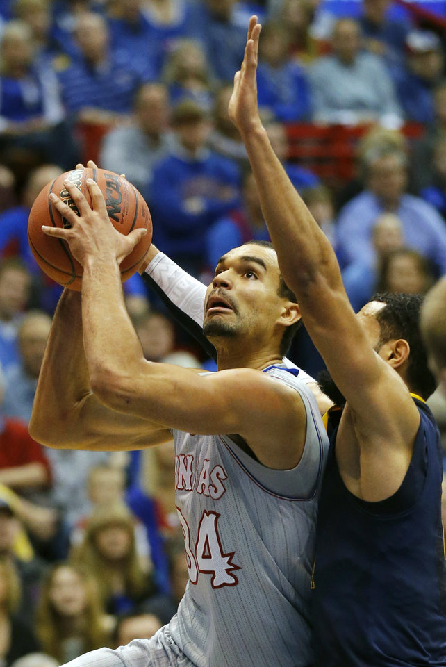 Photo - Kansas forward Perry Ellis (34) shoots while covered by West Virginia forward Remi Dibo, right, during the first half of an NCAA college basketball game in Lawrence, Kan., Saturday, Feb. 8, 2014. (AP Photo/Orlin Wagner)