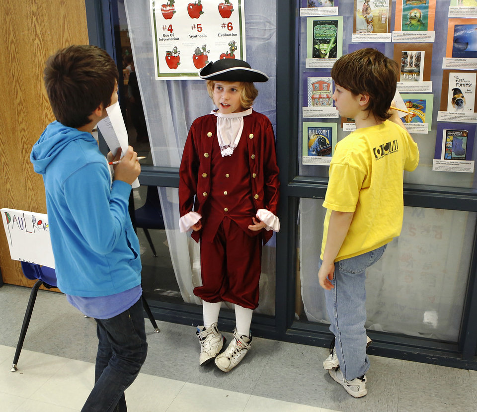 Photo - Dressed as  Paul Revere, Hayden Tatum leans against a window as he talks to two boys about Revere's famous late night  ride to warn colonists.  Wearing authentic era attire, students in Rhonda Watkins' fourth and fifth grade social studies classes at Schwartz Elementary School portrayed various figures from the American Revolution period during  a living history museum program in the school's library on Wednesday,  Jan. 30,  2013.  The students selected a historical person from a list provided by Watkins, and  were required to research the subject, write a report and make a verbal presentation about the person. All students in the school were invited to the library to hear the characters tell about their lives.   Photo by Jim Beckel, The Oklahoman