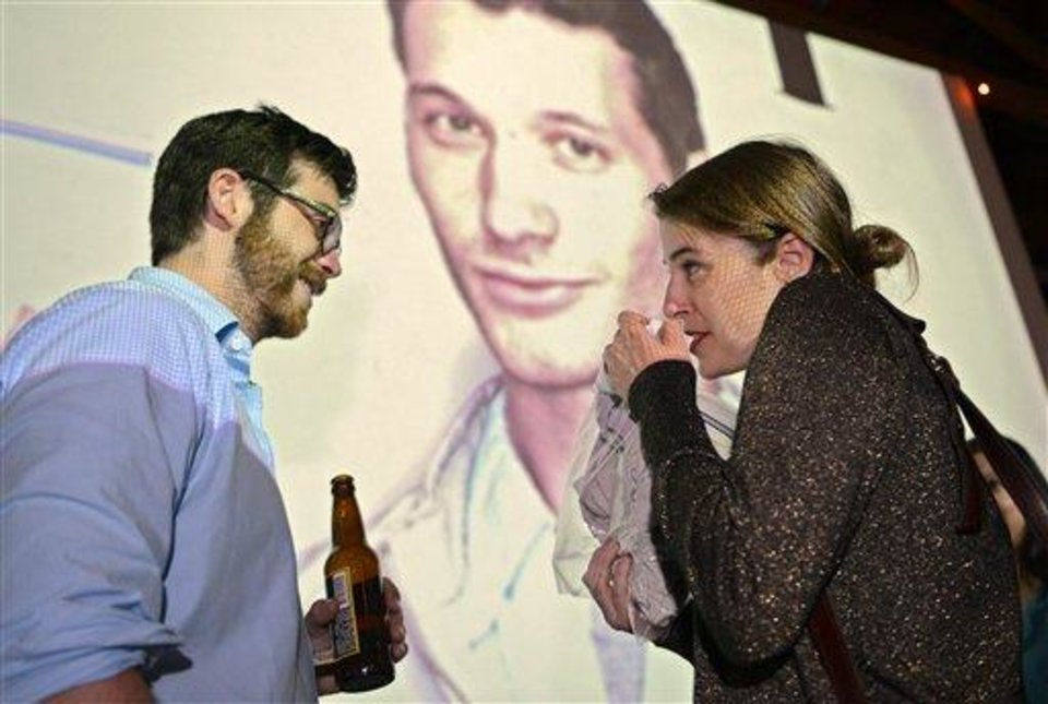 Photo - Scott Yacyshyn, left, talks with Tegan Artho-Bentz she smells a shirt during a pheromone party, Friday, June 15, 2012, in Los Angeles. The get-togethers, which have been held in New York and Los Angeles and are planned for other cities, require guests to submit a slept-in T-shirt that will be sniffed by other participants. Then you can pick your partner based on scent. (AP Photo/Mark J. Terrill)