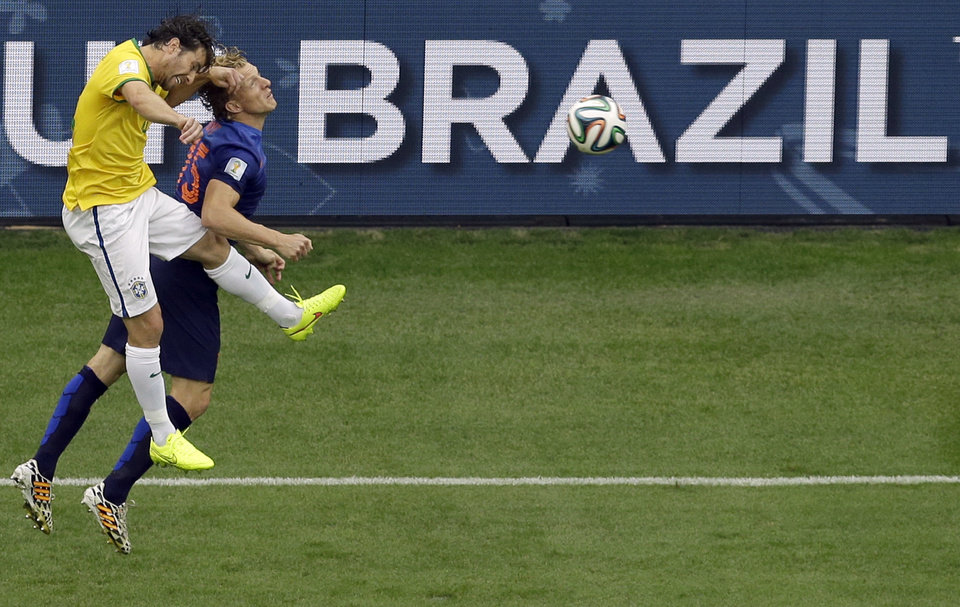 Photo - Brazil's Maxwell, left, and Netherlands' Dirk Kuyt go for a header during the World Cup third-place soccer match between Brazil and the Netherlands at the Estadio Nacional in Brasilia, Brazil, Saturday, July 12, 2014. (AP Photo/Themba Hadebe)