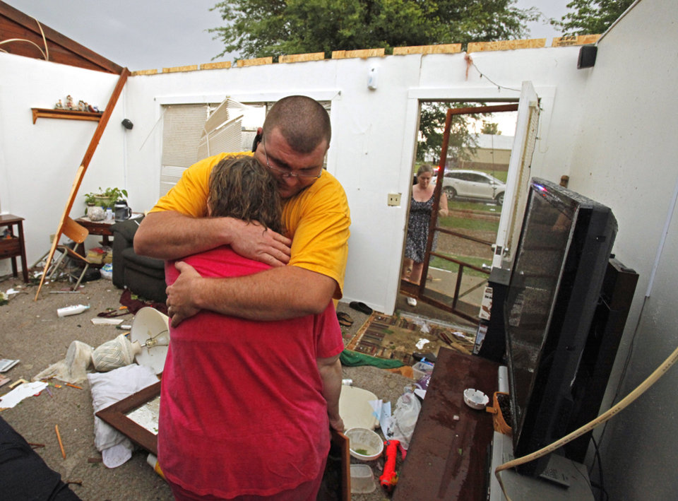Sonny Hale comforts his mother, Debra Lee, on Tuesday after a tornado-spawning storm swept through, tearing off their roof in Newcastle. Photo by Steve Sisney, The Oklahoman