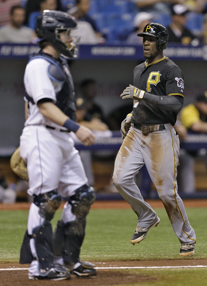 Photo - Pittsburgh Pirates' Starling Marte, right, scores in front of Tampa Bay Rays catcher Ryan Hanigan on an RBI single by Andrew McCutchen off Rays pitcher Alex Cobb during the third inning of an interleague baseball game  Monday, June 23, 2014, in St. Petersburg, Fla. (AP Photo/Chris O'Meara)