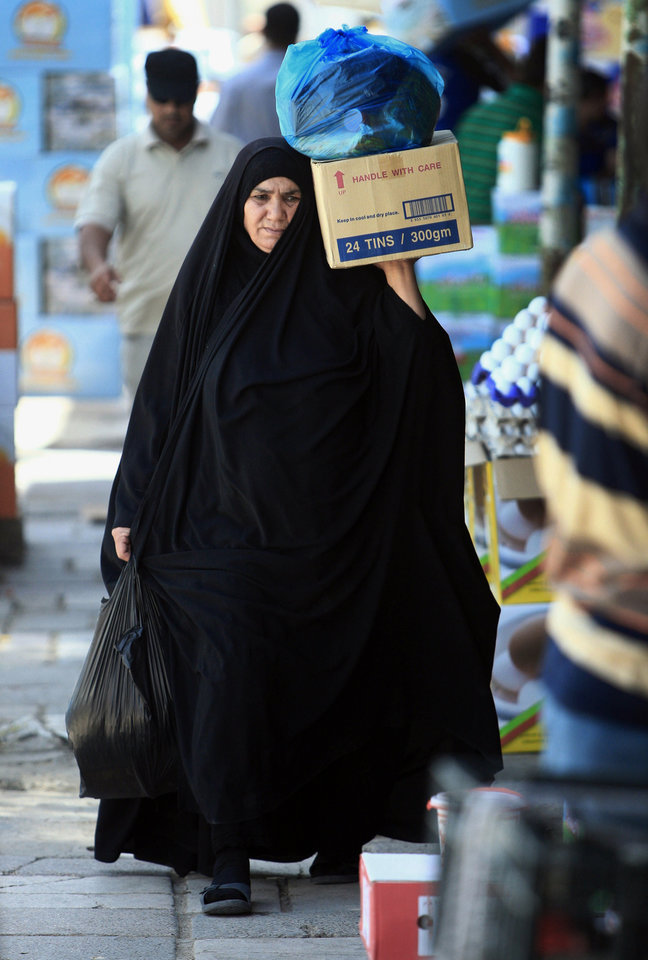 Photo - An Iraqis makes her way at a market in Basra, Iraq's second-largest city, 340 miles (550 kilometers) southeast of Baghdad, Iraq, Thursday, June 19, 2014. Since June 6, Sunni fighters led by an al-Qaida breakaway group, the Islamic State of Iraq and the Levant, have swept through Iraq, seizing the second largest city, Mosul and Saddam Hussein's hometown of Tikrit as thousands of Iraqi soldiers melted away. The insurgents are now pressing to Baghdad. (AP Photo/ Nabil Al-Jurani)