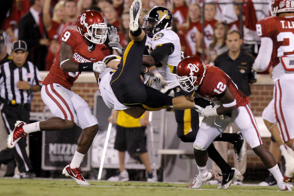 Photo - Oklahoma's Gabe Lynn and Javon Harris bring down Missouri's T.J. Moe during their game Saturday in Norman.  Photo by Bryan Terry, The Oklahoman