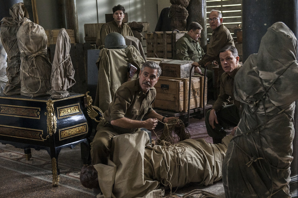 "This image released by Columbia Pictures shows, from left, Dimitri Leonidas, George Clooney, John Goodman, Bob Balaban and Matt Damon in the film, ""The Monuments Men."" The World War II drama opens Friday, Feb 7, 2014.  (AP Photo/Columbia Pictures, Claudette Barius)"