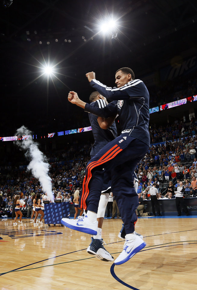 Photo - Oklahoma City's Thabo Sefolosha (2) leaps with Russell Westbrook (0) during player introductions before an NBA basketball game between the Detroit Pistons and the Oklahoma City Thunder at the Chesapeake Energy Arena in Oklahoma City, Friday, Nov. 9, 2012. Oklahoma City won, 105-94. Photo by Nate Billings, The Oklahoman