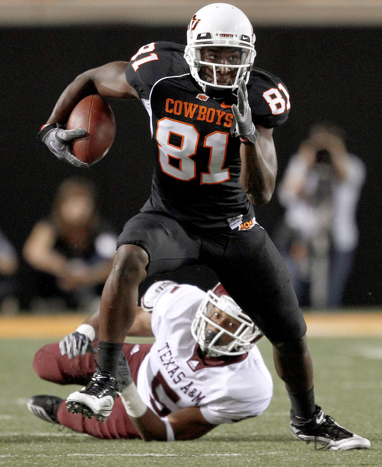Photo - OSU's Justin Blackmon runs past Texas A&M's Coryell Judie during the college football game between Texas A&M University and Oklahoma State University (OSU) at Boone Pickens Stadium in Stillwater, Okla., Thursday, Sept. 30, 2010. Photo by Bryan Terry, The Oklahoman