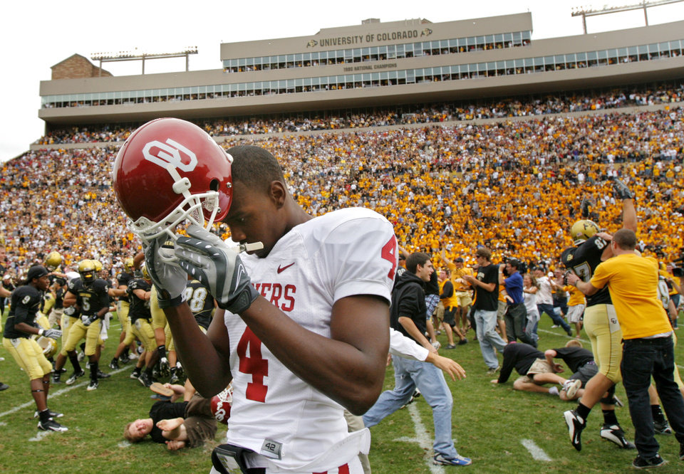 Photo - Oklahoma's Malcolm Kelly (4) takes off his helmet as he walks off the field as Colorado and its fans celebrate the 27-24 upset of over the Sooners during the college football game between the University of Oklahoma Sooners (OU) and the University of Colorado Buffaloes (CU) at Folsom Field on Saturday, Sept. 28, 2007, in Boulder, Co. 