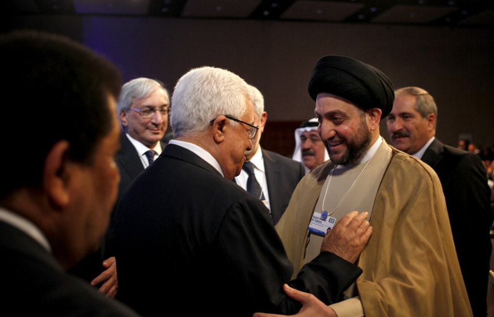 Photo - Palestinian President Mahmoud Abbas, left, greets Ammar al-Hakim, head of the Supreme Islamic Council of Iraq, at the World Economic Forum, held at the King Hussein Bin Talal Convention center, in Southern Shuneh, 34 miles (55 kilometers) southeast of Amman, Jordan, Saturday, May 25, 2013.  (AP Photo/Mohammad Hannon)