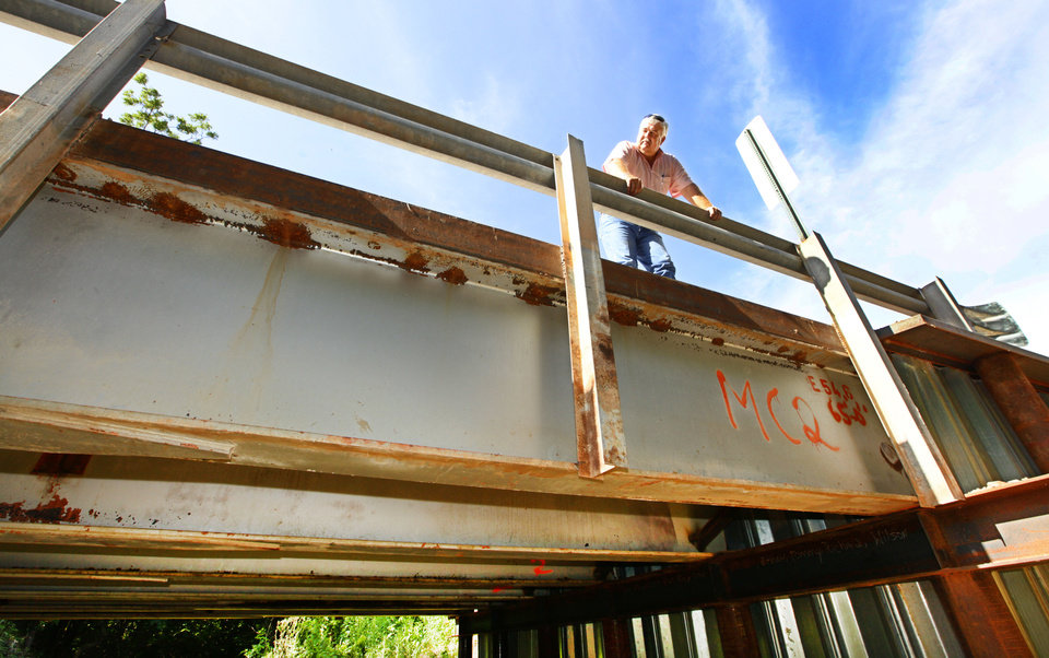 Photo - McClain County District 2 Commissioner Wilson Lyles looks down from a bridge near Washington, OK, that was built using steel beams from the old Interstate 40 Crosstown Expressway.   David McDaniel - THE OKLAHOMAN