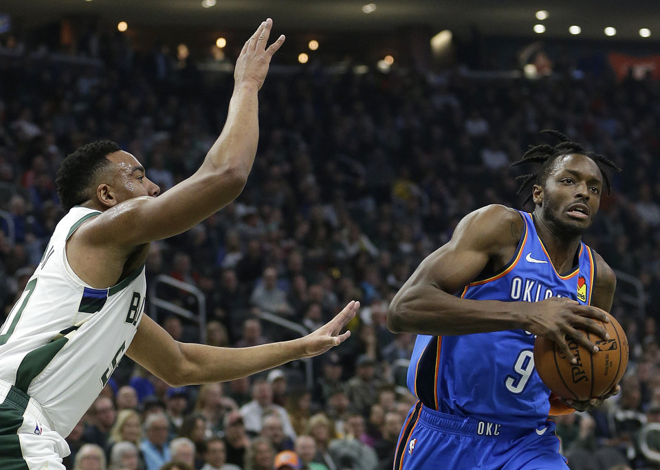 Photo - Oklahoma City Thunder's Jerami Grant (9) drives to the basket against Milwaukee Bucks' Bonzie Colson during the first half of an NBA basketball game Wednesday, April 10, 2019, in Milwaukee. (AP Photo/Aaron Gash)