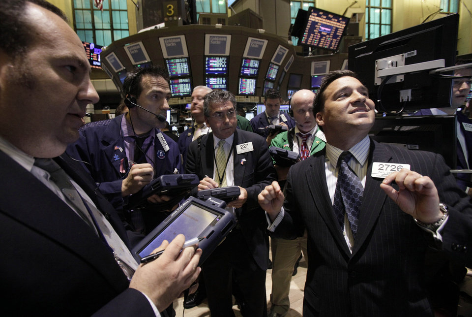 FILE - In a March 21, 2012 file photo, Specialist Paul Cosentino, right, directs trading on the floor of the New York Stock Exchange. Stocks closed mostly lower Tuesday Aug. 14, 2012, after trading slightly higher for much of the day. (AP Photo/Richard Drew,file)