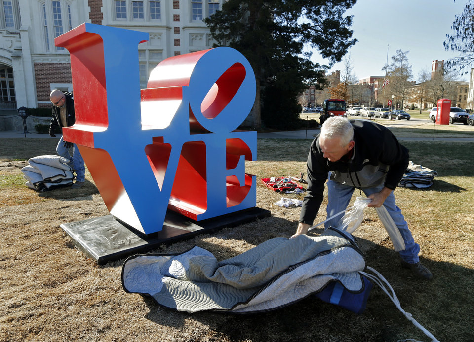 "Photo -  Marty Jackson, OU supervisor of roads and hauling, removes packing from a casting of Robert Indiana's ""LOVE"" sculpture as it is installed in front of the Visitors Center on the University of Oklahoma campus. PHOTO BY STEVE SISNEY, THE OKLAHOMAN   STEVE SISNEY -"
