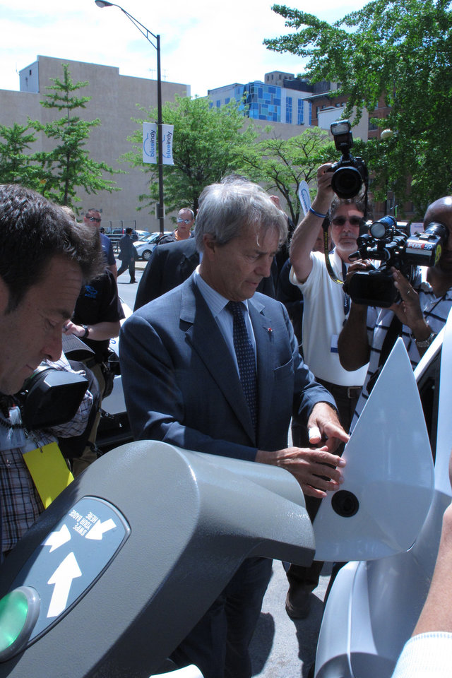 Photo - Bollore Group Chairman Vincent Bollore demonstrate how users of the French company's electric Bluecars will plug in the cars for recharges at a charging station in downtown Indiana. The company debuted its first car-charging station in Indianapolis on Monday, May 19, 2014, that's part of an electric car-sharing service coming to Indiana's capital. Bollore Group is investing $35 million in the project that won't be up and running until year's end, when 125 cars will be available at 25 charging sites around the city. (AP Photo/Rick Callahan)