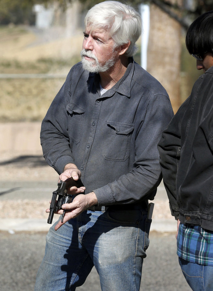 Photo - A gun buyer inspects his purchase outside a police station in Tucson, Ariz. Tuesday, Jan 8, 2013. About a dozen buyers offered cash to sellers in the parking lot of a police station where Tucson City Councilman Steve Kozachik set up a gun buyback program asking people to turn in their guns for a $50 gift certificate to a grocery store. The buyers were trying to purchase weapons from sellers in an effort to circumvent Councilman Kozachik's buyback program. (AP Photo/Matt York)