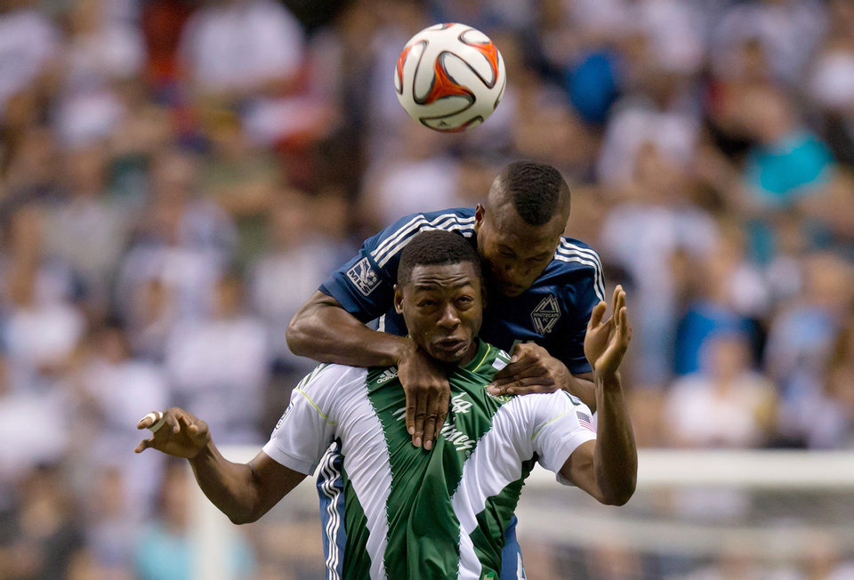 Photo - Portland Timbers' Fanendo Adi, of Nigeria, and Vancouver Whitecaps' Kendall Watson, back, of Costa Rica, vie for the ball during the first half of an MLS soccer game in Vancouver, British Columbia, on Saturday, Aug. 30, 2014. (AP Photo/The Canadian Press, Darryl Dyck)