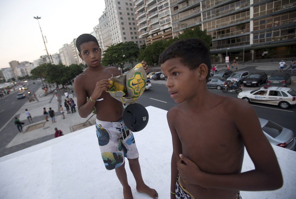 Photo - Elias, 14, left, and Lucas, 11, show their broken ball during a protest demanding better public services and against the upcoming World Cup soccer tournament in Rio de Janeiro, Brazil, Saturday, Jan. 25, 2014. Last year, millions of people took to the streets across Brazil complaining of higher bus fares, poor public services and corruption while the country spends billions on the World Cup, which is scheduled to start in June. (AP Photo/Silvia Izquierdo)