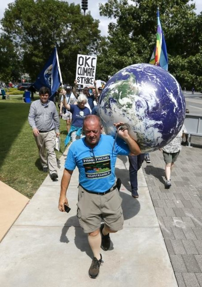 Photo -  Richie Monarch carries an inflatable globe as people march south on Hudson Avenue away from City Hall during the Oklahoma City Climate Strike event, part of global rallies and marches to bring attention to climate change, in Oklahoma City on Friday. [Nate Billings/The Oklahoman]