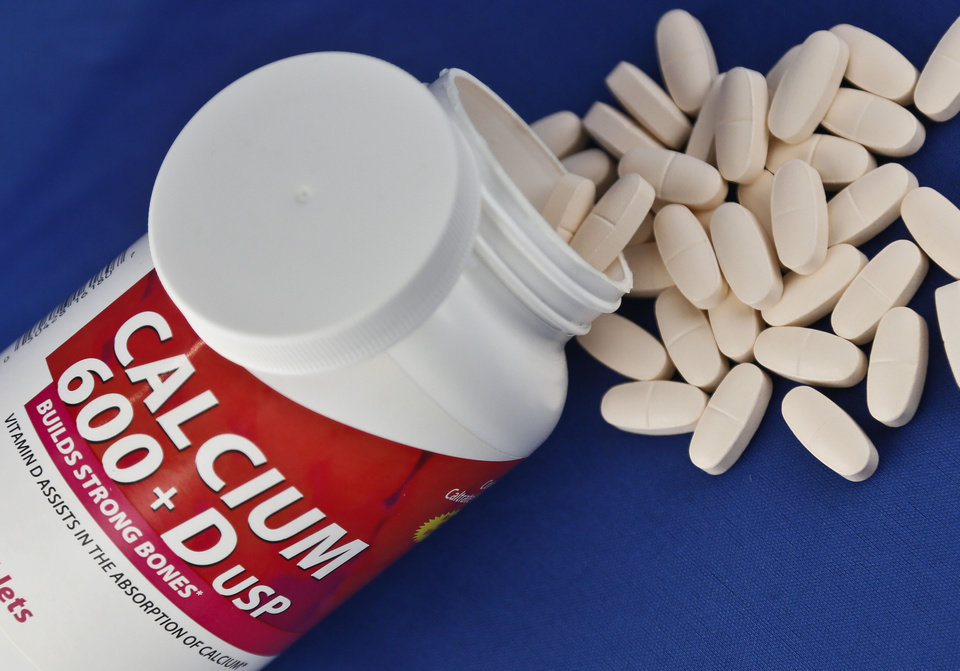 Photo - A photo illustration shows a container of over the counter calcium supplements, Monday, Feb. 25, 2013. A government advisory group says the relatively low doses found in today's dietary supplements don't prevent broken bones in women after menopause. (AP Photo/Bebeto Matthews)