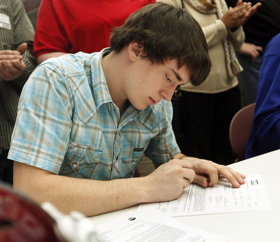 Photo - Justin Marcha signs his letter to play football at Emporia State University during the college signing day ceremony for student athletes at Edmond Memorial High School in Edmond, Okla., Wednesday, Feb. 5, 2014. Photo by Nate Billings, The Oklahoman