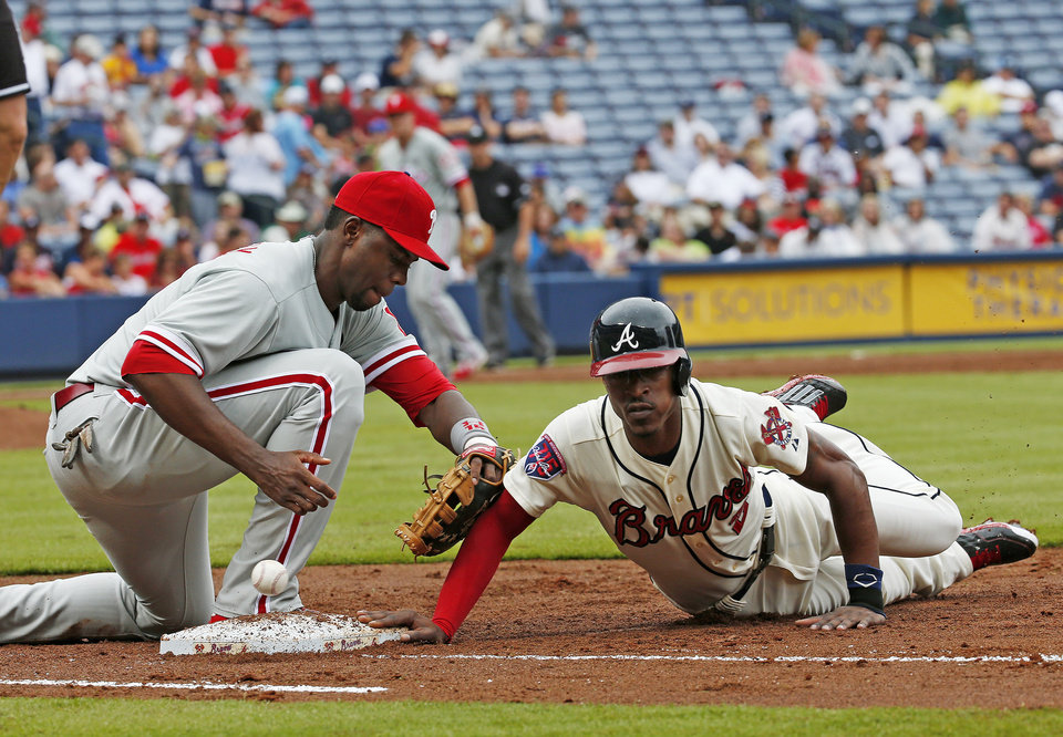 Photo - Atlanta Braves' B.J. Upton (2) dives back to first base as the ball gets away from Philadelphia Phillies first baseman John Mayberry Jr. (15) in the third inning of a baseball game  in Atlanta, Sunday, July 20, 2014. Upton advanced to second on the play. (AP Photo/John Bazemore)