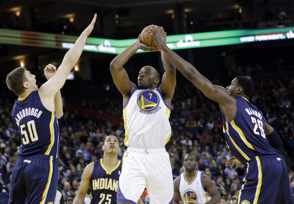 Photo - Golden State Warriors' Carl Landry (7) shoots between Indiana Pacers' Tyler Hansbrough (50) and Ian Mahinmi (28) during the first half of an NBA basketball game in Oakland, Calif., Saturday, Dec. 1, 2012. (AP Photo/Marcio Jose Sanchez)